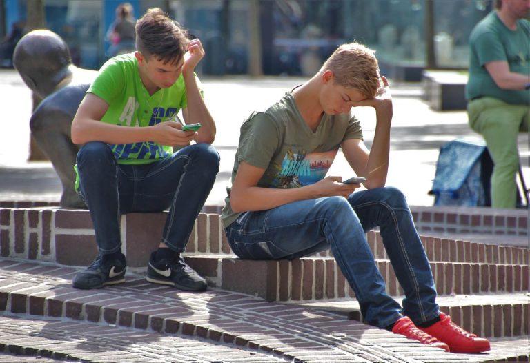 deux adolescents en train de regarder leur téléphone portable